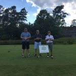 three men posing together while playing golf.